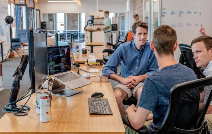 Men sitting at desk in conversation
