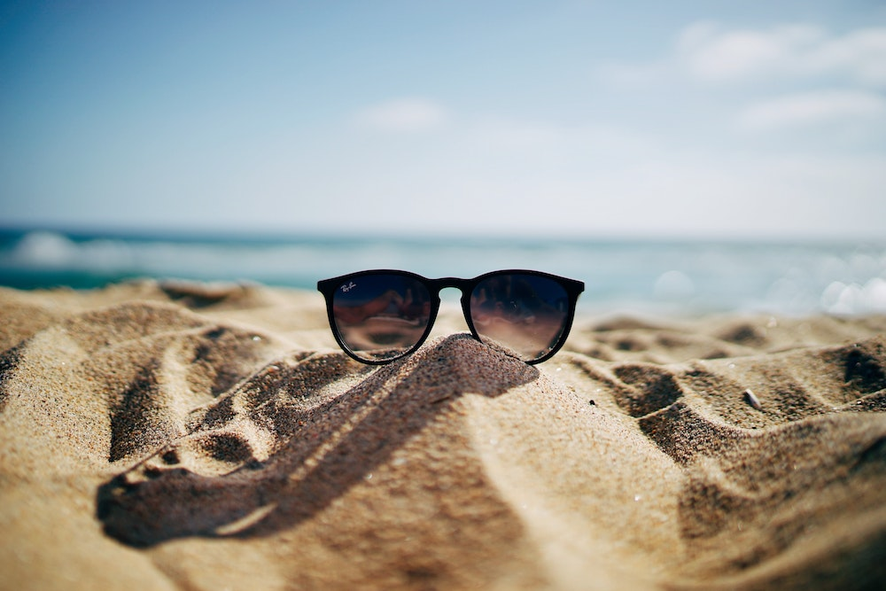 sunglasses on a beach submitting vacation requests
